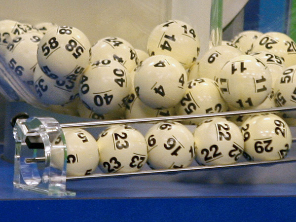 The five balls at the bottom helped two tickets win a $587.5 million jackpot in the Nov. 28, 2012, Powerball drawing. At the time, it was the game´s biggest prize ever. The red Powerball is selected separately. (Phil Sears / Associated Press)