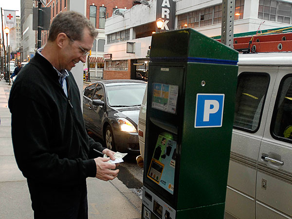Mike McCue uses the parking meter in center city on March 22, 2010. (Ron Tarver / Staff Photographer)