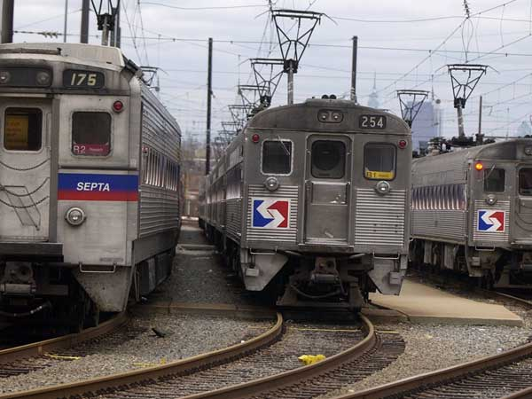 FILE photo: A SEPTA employee working in the Roberts train yard in Nicetown walks past trains waiting to go out  for the PM rush hour. (Ron Tarver / Staff photographer)