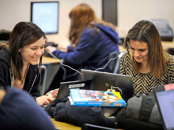 Sophomores Hope Rorer (left) and Lexi Karp share a headphone in the classroom of Nicole Roeder, a cyber program teacher. (Tom Gralish/Staff)