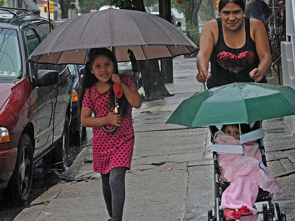 Emilia Hernandez braves a downpour with children Lindsay, 6, and Itzel, 3, at Seventh and Shunk Streets in S. Philadelphia. The heavy rain on Sunday brought road closures in the region and airport delays and contributed to record summer rainfall in Philadelphia. (April Saul/Staff)