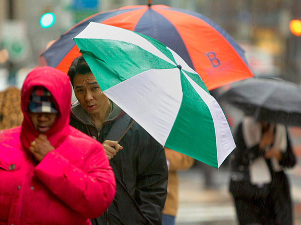 File photo: Philadelphians hunkered under their umbrellas at 18th and Market. (Ed Hille / Staff Photographer)