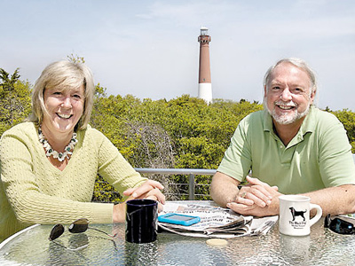 Sarah Ann Miller and Dave Bossi on the third-floor balcony of their Barnegat Light home, with the lighthouse as a backdrop. Other spots in the house, a 1 1/2-year project, offer views of the inlet and the state park. (Akira Suwa / Staff Photographer)