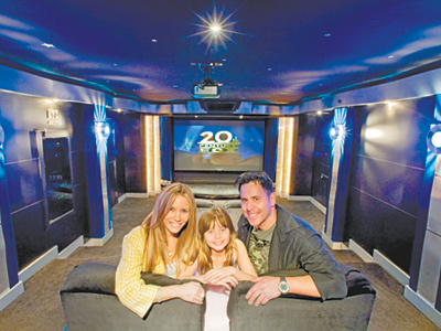 (From left) Lisa, Halie, and Mark Oser in the theater of their Bucks County home. (Clem Murray / Staff Photographer)
