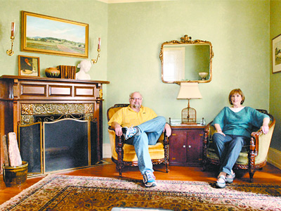 Dean Hartung and Ellen Hutchinson in the living room of their 1889-vintage home in Mount Airy. Found household items and furnishings fill their rooms not only with singular pieces, but with stories of discovery. (Ron Tarver / Staff Photographer)
