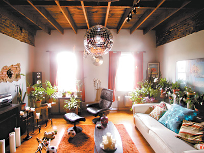 Sunlight pours into the house, and the disco ball hanging from the exposed beams of the living room ceiling delights party guests. (David Swanson / Staff Photographer)