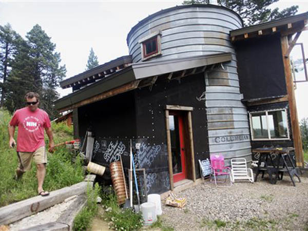 This July 3, 2013 photo shows Park County resident Jeff Moore, who has built an energy-efficient, mountain home using recycled materials on the Bozeman pass, about six miles up Orea Creek Road. (AP Photo/Livingston Enterprise, Shawn Raecke)