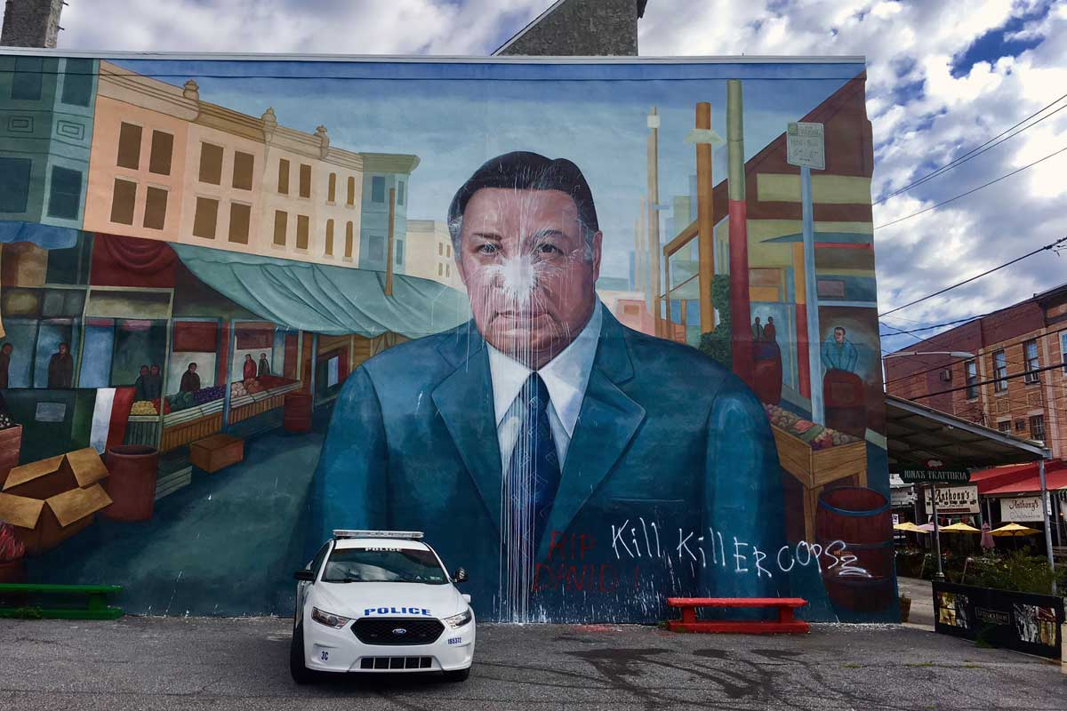 A police car is parked in front of the Frank Rizzo mural Saturday morning after it was vandalized in South Philadelphia.