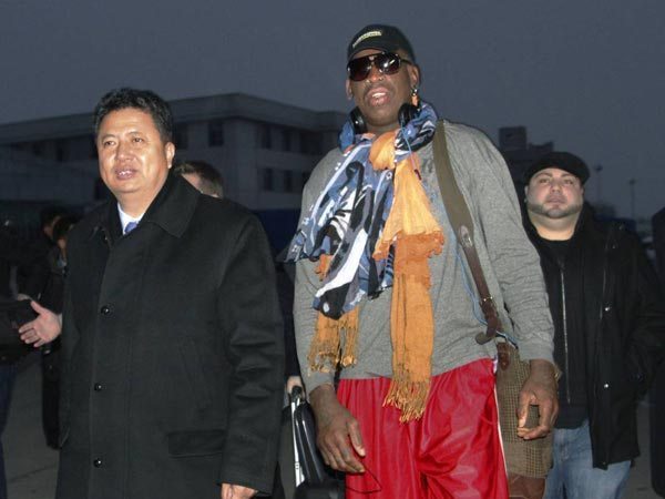 Former NBA basketball star Dennis Rodman walks with Vice Minister of North Korea´s Sports Ministry, Son Kwang Ho, as Rodman arrives at the international airport in Pyongyang, North Korea on Thursday, Dec. 19, 2013. (AP Photo/Kim Kwang Hyon)