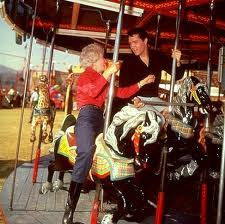 "Barnara Stanwyck and Elvis Presley ride the carousel in ""Roustabout"""