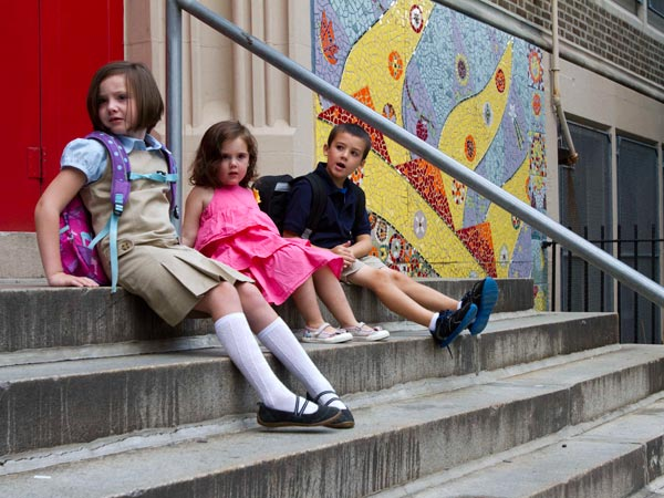 First-graders (left) Claire Dwyer, 6, and (right) Giovanni Piscitelli, 6, sit on the steps of Andrew Jackson Elementary School in Philadelphia. In the center is Claire´s sister, Celeste Dwyer, 3, September 3, 2013.  (DAVID M WARREN / Staff Photographer)