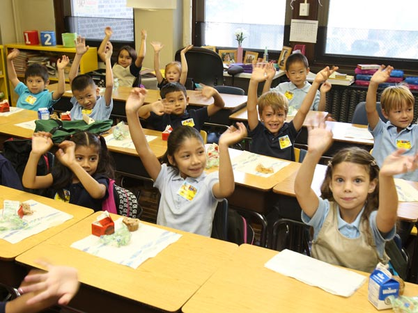 "First-grade students raise their hands to show their ""jagular"" paws (school´s mascot) at Andrew Jackson School in Philly in September 2013. A stepped-up effort by the city to collect the little-known School Income Tax, appears to be working. Just over 37M was collected from this tax, which benefits schools, in the last fiscal year. ( CHARLES FOX / Staff Photographer )"