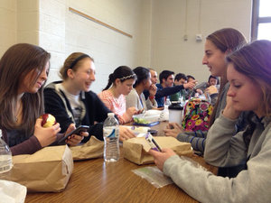 Students at lunch on Facebook on their cell phones and conversing face-to-face. Credit Meghan Miller<br />