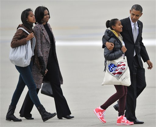 Barack Obama walks with daughters Sasha, right, Malia, Left, and first lady Michelle Obama to Air Force One before leaving O´Hare International Airport in Chicago, Wednesday, Nov. 7, 2012. AP Photo/Paul Beaty)