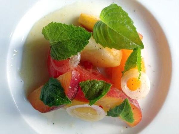 Sbraga pairs its heirloom tomatoes with peaches, raw white onion and a white soy-Thai chili vinaigrette.
