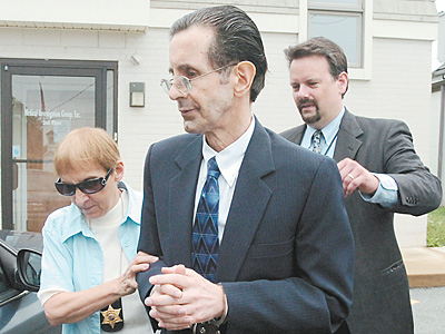Richard A. Brown (center) is led away in handcuffs and leg irons from District Court in Devon by deputy constable Patricia Kurdert (left) and PA narcotics agent Robert R. Semach in June 2008.
