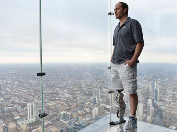 "Zac Vawter, fitted with an experimental ""bionic"" leg, looks out from the Ledge at the Willis Tower, Thursday, Oct. 25, 2012 in Chicago. Vawter is training for the world´s tallest stair-climbing event where he´ll attempt to climb 103 flights to the top of theWillis Tower using the new prosthesis. (AP Photo/Brian Kersey)"
