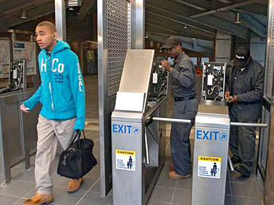 SEPTA has big plans for its new fare system - some day. Here, revenue maintence workers program the gates at the 63rd St. Station. ( Clem Murray / Staff Photographer / FILE )