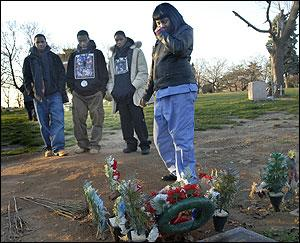 Comforted by his friends, Diane Adams makes her monthly visit to the yet-unmarked grave of her son Kareek. He was 16.