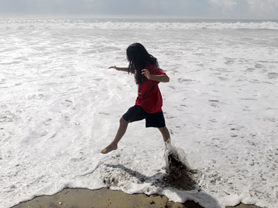 Grace Platt, 10 from Germantown skips through the surf in Ocean City. (Ron Tarver / Staff Photographer)
