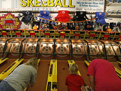 Skee-Ball wizards: Taking a roll at Mariner's Arcade on the Wildwoods boardwalk are, from left, Dee Dzwoniarek, Renee Majewski, 7, and her mom, Michelle Majewski. Skee-Ball is 100 years old this year. (MICHAEL S. WIRTZ / Staff Photographer)