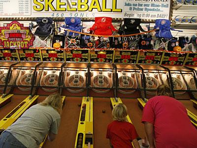 Skee-Ball wizards: Taking a roll at Mariner's Arcade on the Wildwoods boardwalk are, from left, Dee Dzwoniarek, Renee Majewski, 7, and her mom, Michelle Majewski. Skee-Ball is 100 years old this year. (MICHAEL S. WIRTZ / Staff Photographer)
