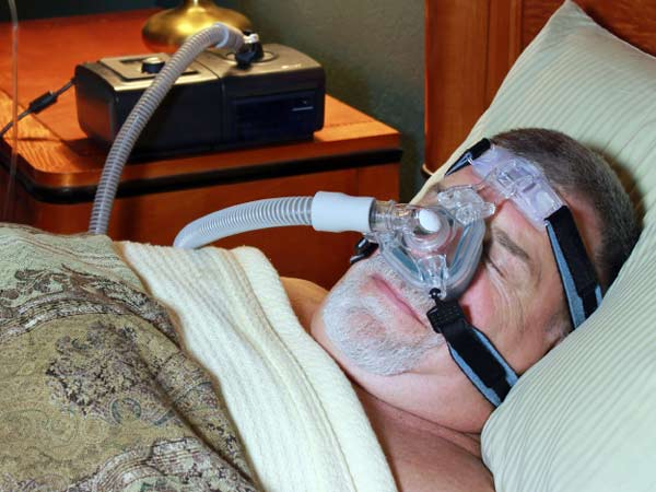 Man treating his sleep apnea while he sleeps.