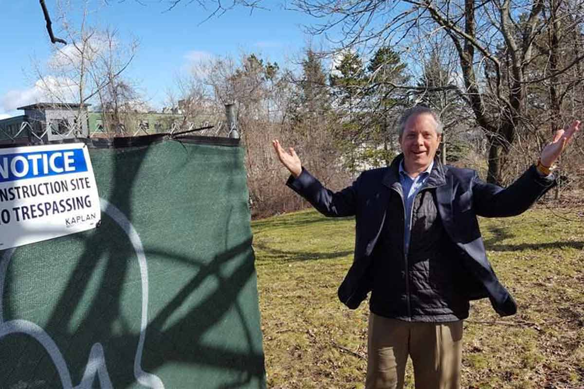 Bart Mitchell, who coordinates affordable housing projects in Boston, gestures to an empty lot where a new project is to be built. Financing for the project was thrown into disarray by the prospect of lower federal corporate tax rates.<br />