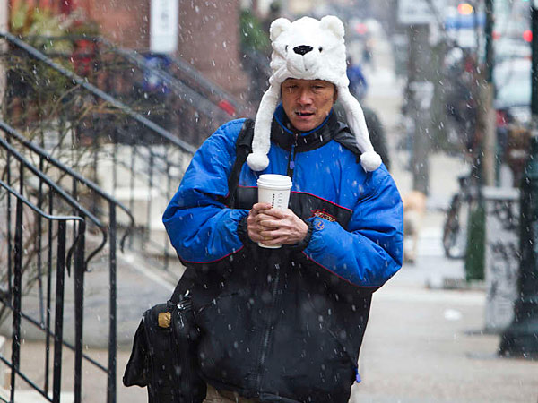 Ready for the cold, a man scurries down the 1600 block of Spruce Street on Thursday, Jan. 16, 2014, dodging snowflakes while carrying a hot beverage and wearing a polar bear hat. (Ed Hille/Staff)