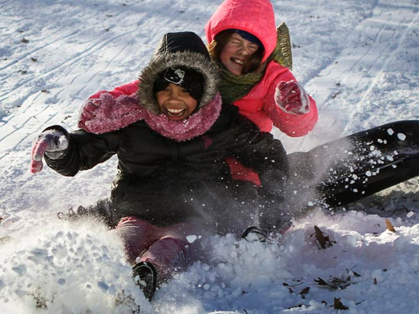 Eleven-year-old Giana Matthews11 (left) and 8-year-old Sophia Grasela slip off their sled while riding down a hill in Clark Park in West Philadelphia on Friday, Jan. 3, 2014. It was a snow day for Philadelphia public schools.  (Stephanie Aaronson / Philly.com)