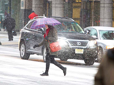 Pedestrians make their way through center city near City Hall as snow begins to fall on Friday afternoon. This is the scene at 15th and Market Streets. ( ED HILLE / Staff Photographer )