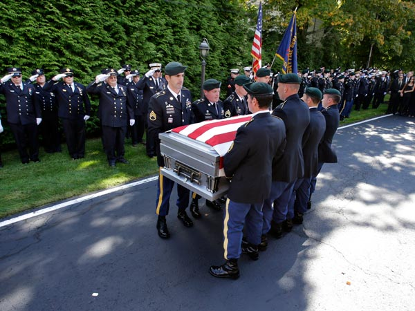 A U.S. Army honor guard carries the coffin of Army Staff. Sgt. Timothy McGill after a procession through his hometown of Ramsey, N.J., With the government shutdown, families will not receive the benefits needed to assist in military funerals. (AP Photo/Mel Evans, file)
