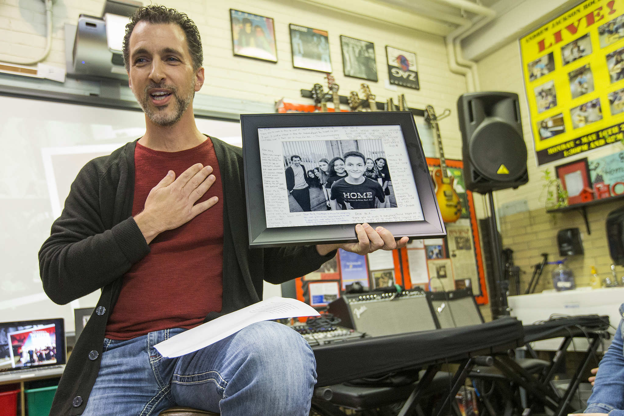 Music teacher Chris Argerakis holds up a photo of HOME as he talks about the band. HOME, the acclaimed, improbable rock band made up of students from Jackson Elementary, a Philadelphia public school, is the subject of a new documentary that airs on WHYY this week. We attend the screening at Jackson Elementary ion Oct. 26, 2017.