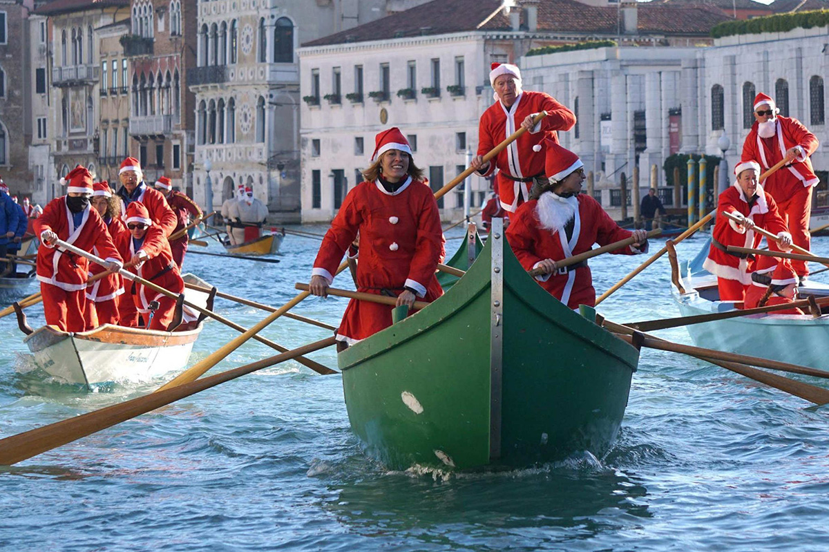 People wearing Santa Claus costumes row on Canal Grande in Venice, Italy, Sunday, Dec. 17 2017. Almost a hundred traditional rowing boats, of various kinds and sizes, for about two hundred rowers, gave life to the traditional water procession of the Santa Claus, parading along the Grand Canal.