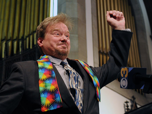 Defrocked United Methodist minister Frank Schaefer, wearing a rainbow stole for solidarity with LGBT people, does a little dance in celebration at a press conference where he announced the church had reinstated his credentials June 24, 2014. ( CLEM MURRAY / Staff Photographer )
