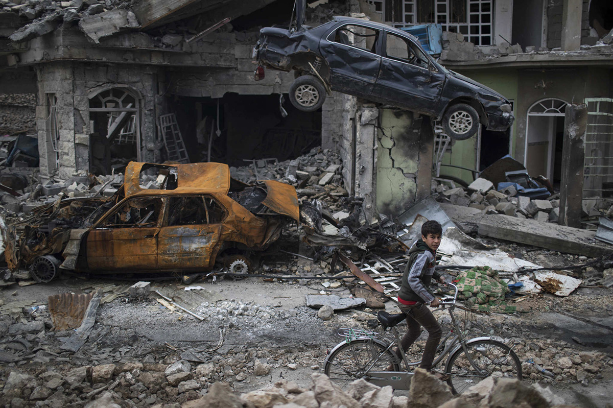 2017 AP YEAR END PHOTOS - A boy rides his bike past destroyed cars and houses in a neighborhood recently liberated by Iraqi security forces, on the western side of Mosul, Iraq, on March 19, 2017.