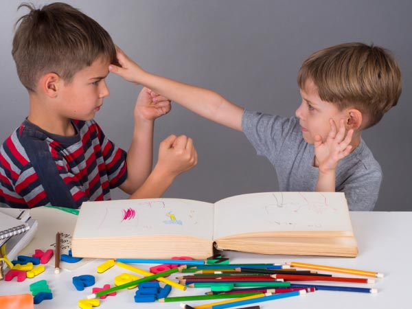 Two young boys arguing at school.
