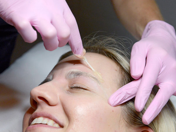 Danielle Ghan peels of a sugaring substance used to shape the brows of Kathleen Luppi in Huntington Beach, Calif, on May 22, 2014. Sugaring is an alternative to waxing. (Christine Cotter/Orange County Register/MCT)<br />