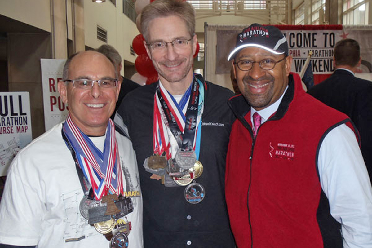 Mark Sullivan (center) and Bob Koen (left) wearing all 19 Philly Marathon finisher medals next to Mayor Nutter at the 2012 opening ceremonies.