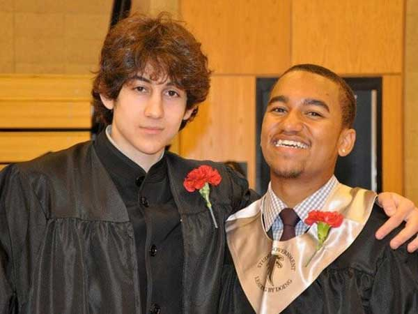 In this undated photo provided by Robin Young, Dzhokhar A. Tsarnaev, left, and Here & Now host Robin Youngís nephew, right, pose for a photo after graduating from Cambridge Rindge and Latin High School. Tsarnaev has been identified as the surviving suspect in the marathon bombings. Two suspects in the Boston Marathon bombing killed an MIT police officer, injured a transit officer in a firefight and threw explosive devices at police during a getaway attempt in a long night of violence that left one of them dead and another still at large Friday, April 19, 2013. (AP Photo/Robin Young)
