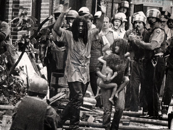 """LET THE FIRE BURN"": MOVE members and children emerge from their ""headquarters"" in a 1978 confrontation. ( Sam Psoras / Philadelphia Daily News )"