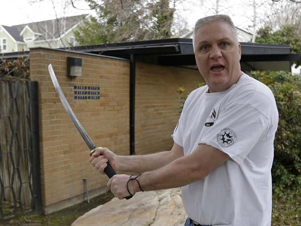 Kent Hendrix, 47, draws his sword near his house.  (AP Photo/Rick Bowmer)