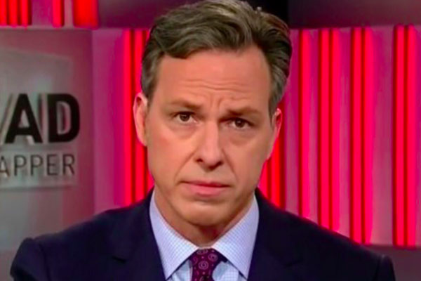 CNN anchor Jake Tapper reacts with a pained facial expression while interviewing Kellyanne Conway.