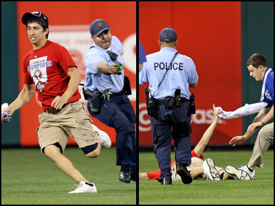 A Philadelphia police officer with Taser in hand chases a Phillies´ fan, now identified as Steve Consalvi, who ran on the field during Monday night´s game. Consalvi was felled by a taser. (Steven M. Falk / Staff Photographer)