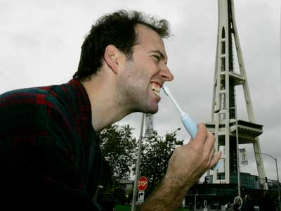 Dan Buchholz brushes his teeth Tuesday, Oct. 2, 2007, near the Space Needle in Seattle using a portable sink and mirror that he brought with him. Buchholz was one of five local people recruited to brush their teeth in various public locations around Seattle as part of a performance-art style promotion for an electric toothbrush manufacturer. (AP Photo/Ted S. Warren)