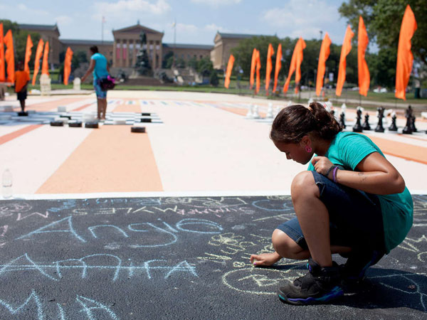 "Nya Glipsy, 10, makes chalk drawings at the Oval. The ""beach"" will be open until Aug. 18. (ANDREW RENNEISEN / Staff Photographer)"