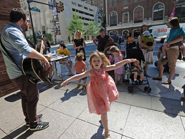 Melaney McAteer, 4, of Philadelphia, dances to the music of the children´s musician Ticklebombs, also known as Shane Walsh, in front of the Kimmel Center, at last year´s Make Music Philly.  (APRIL SAUL / Staff Photographer)