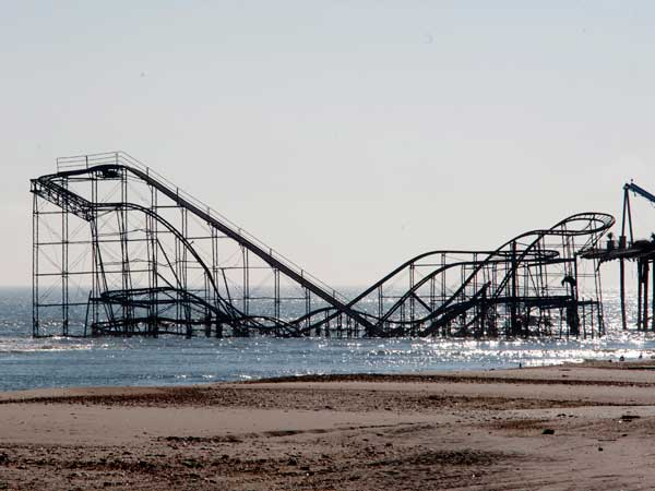 The Jersey shore two weeks after Hurricane Sandy on Nov. 12, 2012.  Here, in Seaside Heights, a sailboat glides by a roller coaster in the ocean.  APRIL SAUL / Staff Photographer