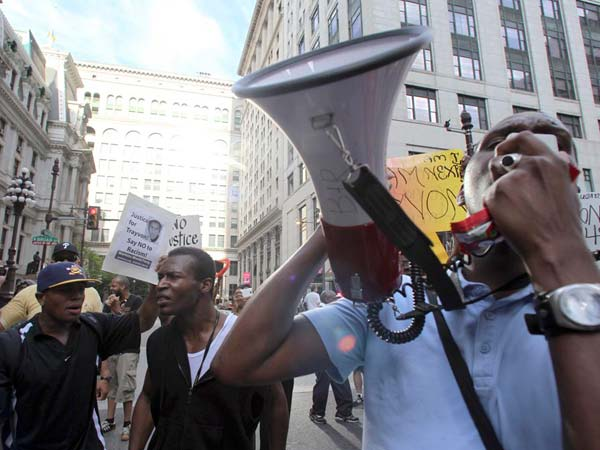 People rally on South Broad Street near City Hall on Sunday, July 14, 2013, in Philadelphia, protesting the acquittal of George Zimmerman in the fatal shooting of 17-year-old Trayvon Martin in Sanford, Fla. (AP Photo/Philadelphia Daily News, Yong Kim)