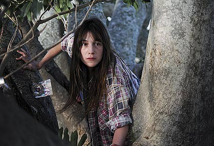 Charlotte Gainsbourg climbs a tree.